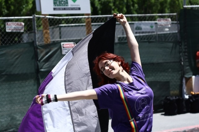photo of a person joyously waving an ace flag