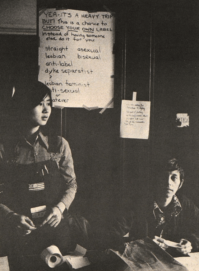 "Photo is of two people attending a table. A sign behind them says ""Yea it's a heavy trip BUT! This is a chance to CHOOSE YOUR OWN label instead of having someone else do it for you: straight asexual lesbian bisexual anti-label dyke separatist ? lesbian feminist anti-sexual or whatever"""
