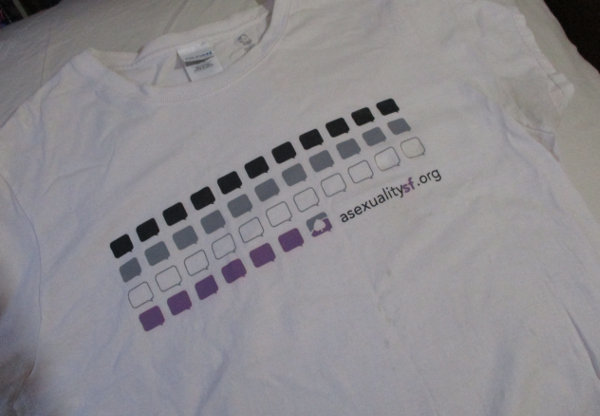 A white t-shirt on top of an off-white fabric. The t-shirt has black, grey, and purple squares printed on it.